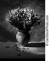 Still life with black and white  bouquet of dried roses in clay vase with grunge background