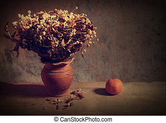 Still life with bouquet of dried roses in clay vase and fruit with grunge background