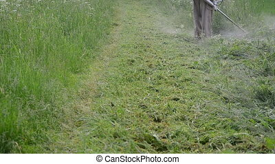 gardener cut grass - Farmer worker man cut trim mow wet high...
