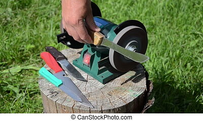 sharpening knives on a rotating electric sharpener outside...