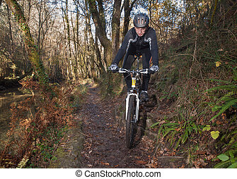 Man practicing mountain bike in the forest in Galicia, Spain...