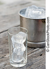 ice cubes - Glass with ice cubes and Ice bucket filled with...