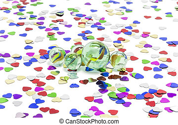Toy marbles on white background, surrounded by so many...