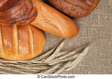 variety of fresh bread with ears of rye