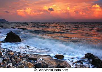 Storm waves crash on a rock in the sunset