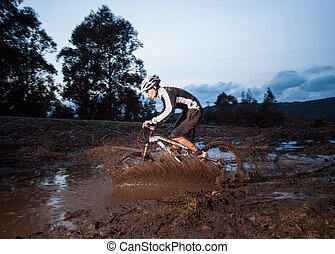 Rider in action at a mud puddle in nature outdoors