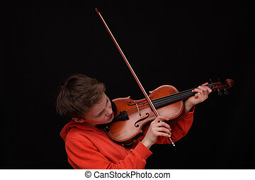 Violinist - Young boy plays violin on black background