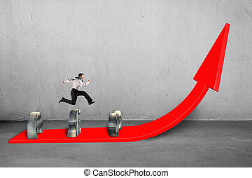Businessman jumping over money symbols on growing red arrow...