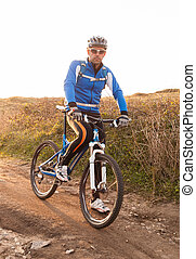 Mountain bike rider looking at camera The rider is standing...