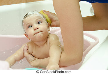 Cleaning baby - Mother cleaning baby at with a sponge