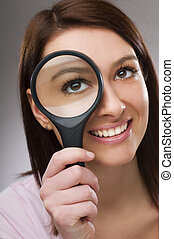 Loupe - Young business woman looking through loupe close up