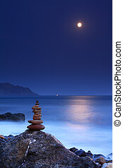 Moonrise over the ocean beach with stack of rocks
