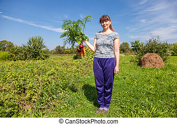 Young woman holding a sheaf of vegetables in the hand