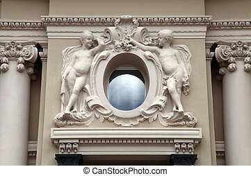 angel statues and oval window at baroque style facade,...
