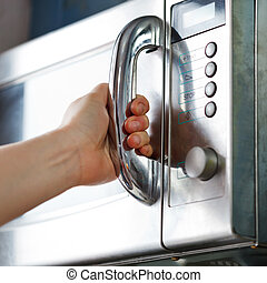 opening of microwave oven door in home kitchen