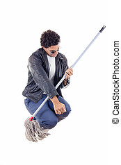 man in leather jacket jumps with a broom