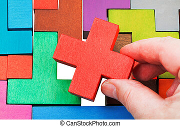 putting cross shaped piece in wooden puzzle - putting cross...