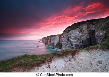 dramatic fire sunrise over cliffs in ocean, Etretat, France