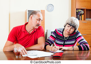 Mature couple calculating family budget at home interior