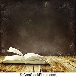 Book - Open book on floor in front of blackboard