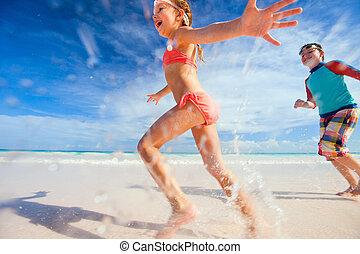 Kids having fun at beach - Happy kids running and jumping at...