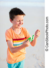 Little boy flying a kite - Close up of boy flying a kite at...
