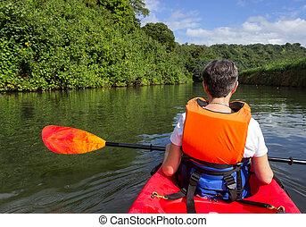Senior lady in canoe approaching Hanalei bridge