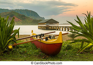 Hawaiian canoe by Hanalei Pier - Red and yellow hawaiian...
