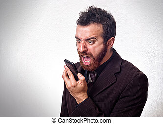 Man in business suit shouting into his mobile phone Business...