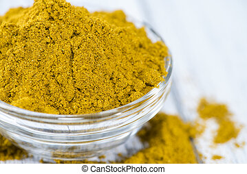 Curry Powder (in a bowl) on white vintage wooden background