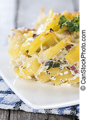 Portion of Potato Gratin on wooden background