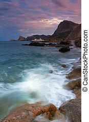 Ocean waves crash against a rock
