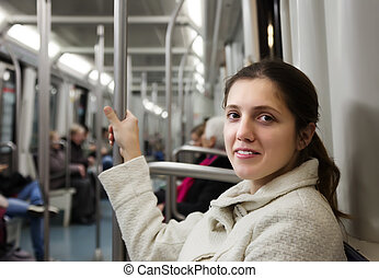 Female passenger in subway train at metro