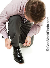 Putting on Shoes - Businessman lacing up his shiny black...