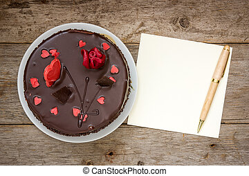 Chocolate cake with note paper and pen