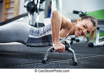 Push-ups - Cute Young girl doing push-ups in gym. Looking At...