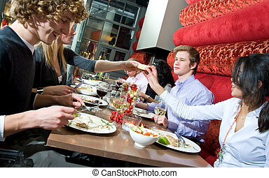 people having dinner - a group of people having dinner in a...