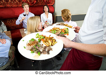 serving dinner - a waiter serving dinner to a group of...