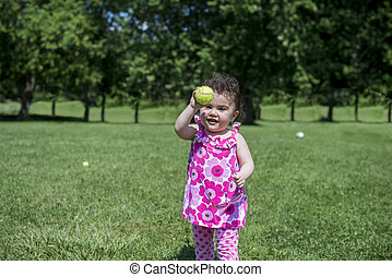 Little Girl Playing with Tennis Bal - Little Girl Wearing...