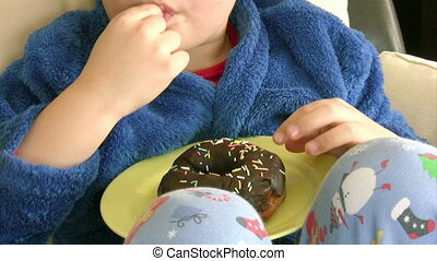Boy likes chocolate donut - Child eating donut and smilimg...