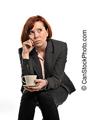 sad business woman with red hair drinking coffee and...