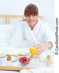 Breakfast in bed - Beautiful woman eating breakfast in bed