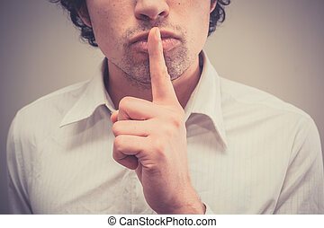 Hush - Young man with finger on lips is gesturing hush