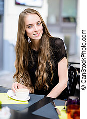 Beautiful woman drinking coffee at the cafe