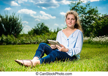 Beautiful young girl using tablet pc and sitting on the green grass