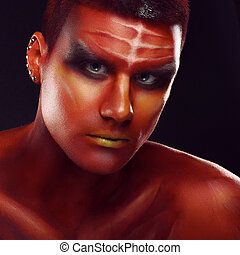 Portrait of a handsome young man in a red body painting
