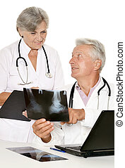 Doctor couple working at table - Elderly doctors with a...