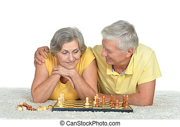 Happy elderly couple playing chess
