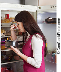 woman  holding her nose because of bad smell near fridge
