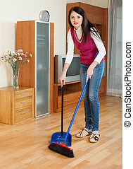 Brunette girl with dustpan and brush at home